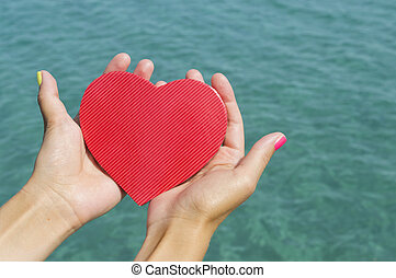 Female hands holding a heart above the sea water