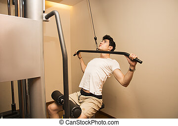 Handsome young man exercising back on gym equipment