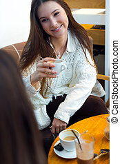 Beautiful young woman drinking coffee in cafe shop.