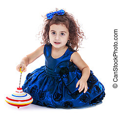 Dark-haired curly-haired little girl spinning dreidel...
