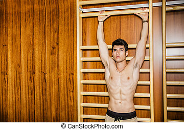 Young man hanging from gym equipment - Attractive young man...