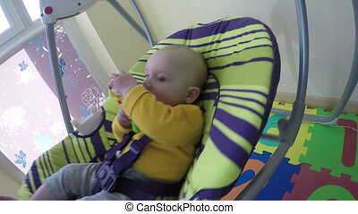 cute baby in swing - cute baby with toy in hand sway in...