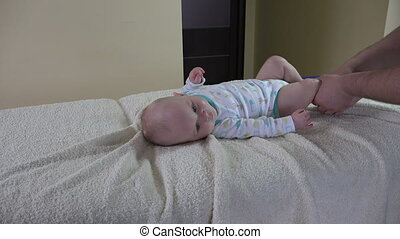 masseur massage baby - Male physiotherapist massaging infant...