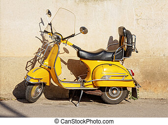 Yellow Vespa - yellow retro motorcycle standing against wall