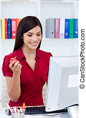 Smiling businesswoman holding a red apple at her desk