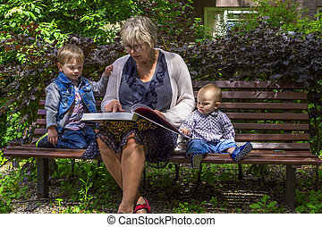 Grandmother reading to her grandchildren in the park