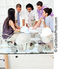 A group of architects studying plans in a meeting with...
