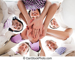 Smiling business team in a circle with heads together...