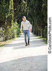 Handsome young man walking along rural road with hoodie,...