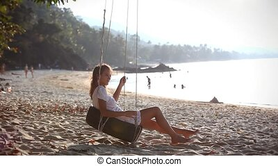 Girl swinging and relaxing on a wheel near the beach