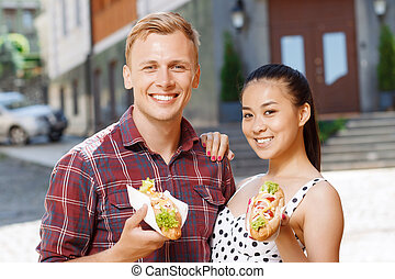 Young man and woman with hotdogs on street - Going to eat...