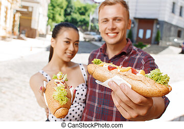 Young man and woman with hotdogs on street - Look at it...