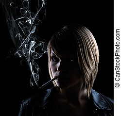smoking woman on black background - low key shot of a...