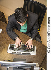 Young businessman in office desk using computer