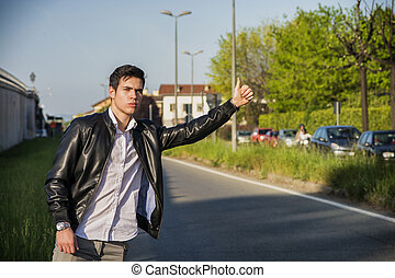 Handsome young man, hitchhiker waiting on roadside -...