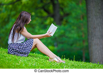 Young girl reading a book outside in park