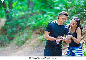 Young active couple looking at smart watch heart rate...