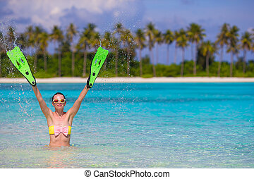 Travel beach fun concept - woman holding snorkeling fins...