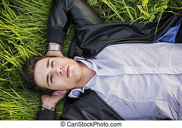 Good looking, fit male model relaxing lying on the grass -...