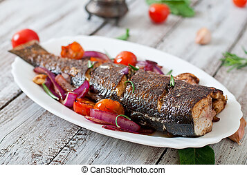 Roasted seabass with vegetables on an old wooden background.