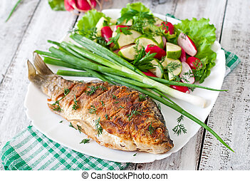 Fried fish carp and fresh vegetable salad