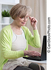 Woman using laptop - Elderly woman using her laptop at home