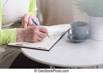 Writing down in notebook - Senior woman writing down the...