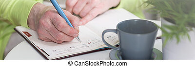 Close-up of notebook - Close-up of aged woman checking the...