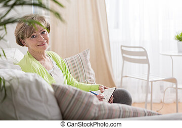 Noting the ideas - Middle aged creative woman noting her...