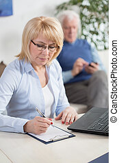 Income and expenditure planning - Middle-aged woman...