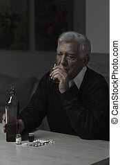 Drinking whiskey and taking pills - Lonely old man drinking...