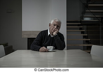 Sad senior man sitting at the table