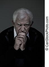 Sad senior man praying - Vertical view of sad senior man...