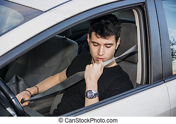 Young man in car fastening seat belt for safety