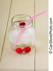 Cold cherry drink in jar with pink straw - Vertical photo of...