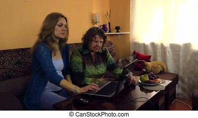 woman granny use laptop - young granddaughter show her...