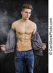 Attractive muscular trendy young man undressing