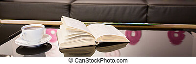 Close-up of coffee table - Panoramic view of book and tea on...