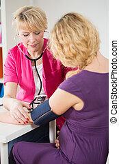 Pregnant woman having pressure measured - Pregnant woman at...