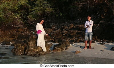 bride sits on rock  and groom looks from beach at sunrise