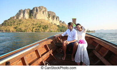 bride and groom float in longtail boat to island at sunrise...