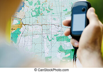 Man holding a GPS receiver and plan in his hand Handheld GPS...