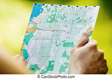 Man holding a map in his hand. - Man holding a map in his...