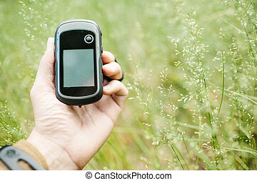Man holding a GPS receiver and plan in his hand. Handheld...
