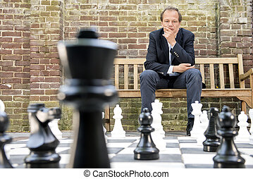 Thinking man sitting at a life sized outdoor chess board -...