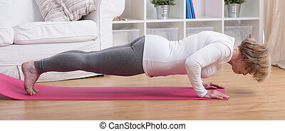 Woman and sun salutation - Aged exercising woman during yoga...
