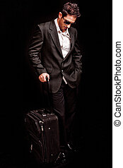 Business man looking down with his luggage on black isolated...