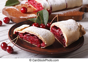 Pieces of strudel with cherry close-up on a plate. horizontal