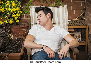 Handsome young man in balcony sleeping on chair wearing a...