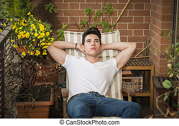 Handsome young man in balcony day-dreaming, sitting on chair...